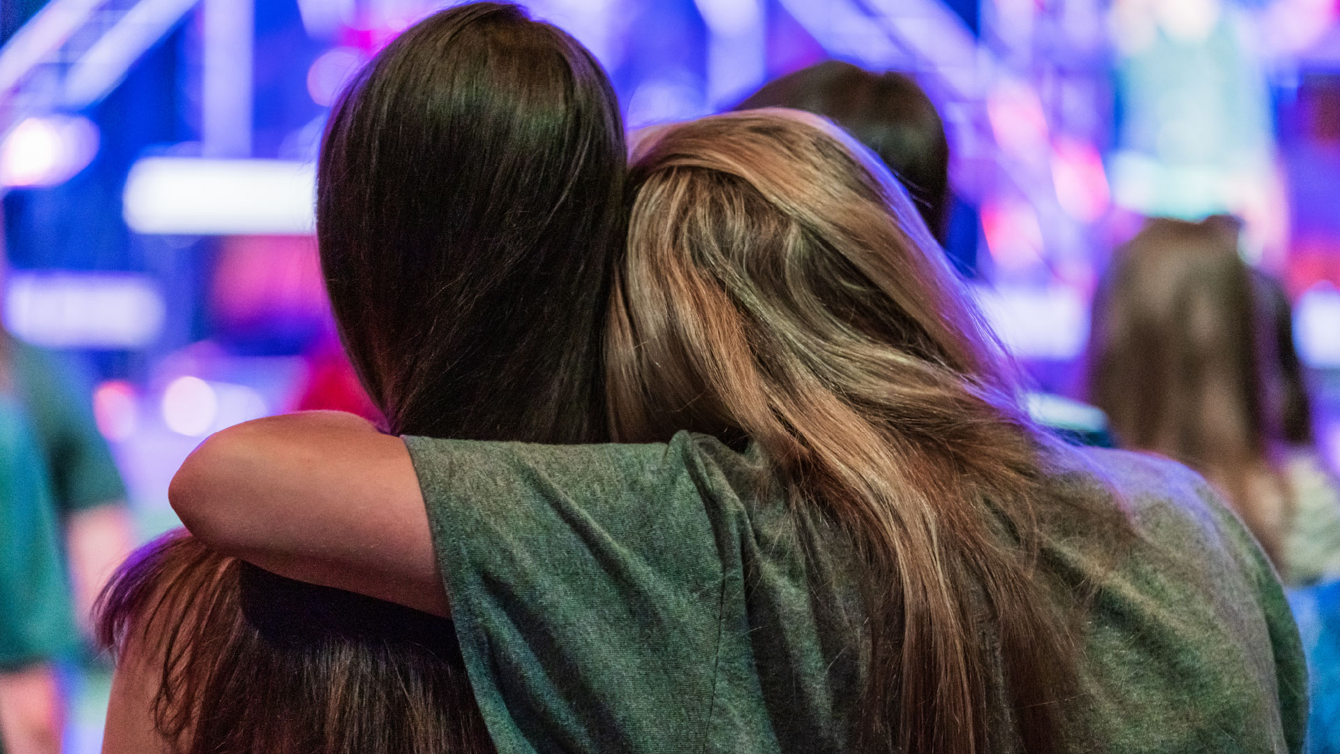 Two 7th grade friends hugging during an Axis meeting at Brookwood Church