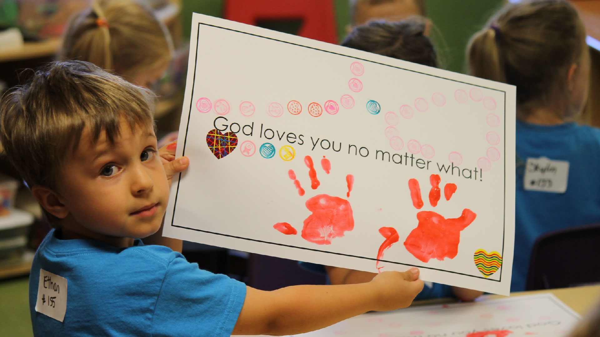 A young boy holds up a picture that he drew at Brookwood Church BrookwoodKiDs