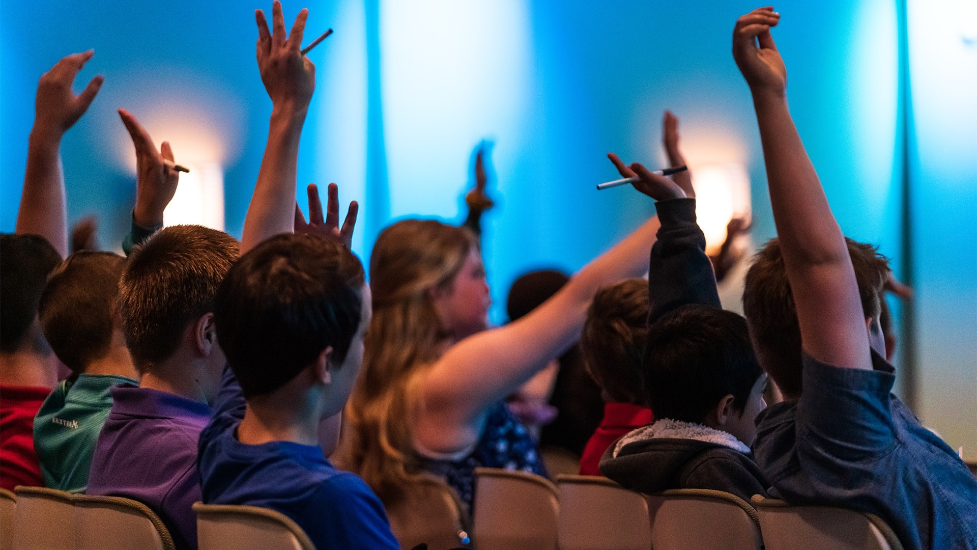 Students raise their hands at a Sunday meeting at Brookwood Church